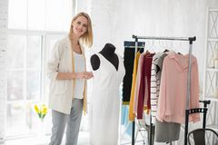 Positive female dressmaker working on dress. Accessories leaving. Jovial female dressmaker grinning to camera while touching dress stock photography
