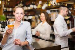 Positive female drinking wine at counter Stock Photography
