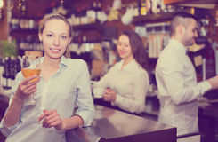 Positive female drinking wine at counter. Positive american female drinking wine at counter stock photos