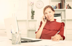 Positive female employee answering on phone and taking notes. Young positive female employee answering on phone and taking notes at office Royalty Free Stock Image