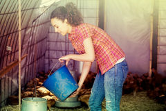 Positive female farmer giving feeding stuff Stock Photo