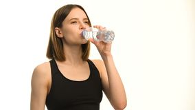 Positive female fitness model after workout drinking water in studio over white background. stock video footage