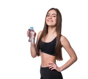 Positive female fitness model after workout holding a bottle of pure water over white background. Royalty Free Stock Photography