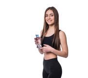 Positive female fitness model after workout holding a bottle of pure water over white background. Stock Images