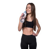 Positive female fitness model after workout holding a bottle of pure water over white background. Royalty Free Stock Photo