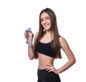 Positive female fitness model after workout holding a bottle of pure water over white background. Stock Image