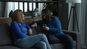 Positive female friends enjoying free time at home stock footage