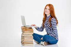 Positive female put laptop on books and using it. Positive attractive young redhead female put laptop on books and using it over white background Royalty Free Stock Images