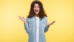 Pretty young woman with curly hair screaming in a surprise and got happy, over yellow background stock images