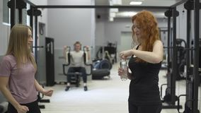 Positive female trainer giving bottle of water to the redhaired woman in the gym. The girl working with personal trainer. Positive female trainer giving a bottle stock footage