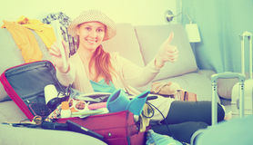 Positive female traveler packing suitcase for holiday Royalty Free Stock Photography