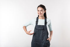 Positive female worker standing against grey background Stock Photo