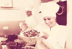Positive female young cook holding plate. Positive female young cook wearing uniform holding plate with green salad Stock Photos