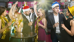 Positive females and males celebrating new year. In the club at night Royalty Free Stock Photo