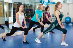 Positive females working out at aerobic class in modern gym. Positive cheerful females working out at aerobic class in modern gym for women Royalty Free Stock Images