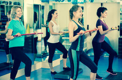 Positive females working out on aerobic step platform royalty free stock images