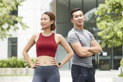 Positive fitness trainers. In sports clothes standing outdoots stock images