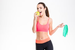 Positive fitness woman holding measuring tape and eating an apple Royalty Free Stock Photography