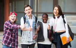 Positive four friends with folders and backpacks Stock Image