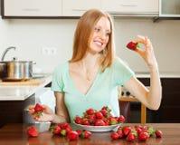 Positive Frau, die Erdbeere im Haus isst Lizenzfreie Stockfotos