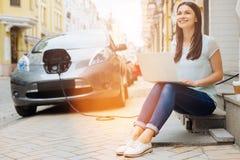 Positive Frau, die an Laptop beim Warten auf Auto arbeitet Stockfoto