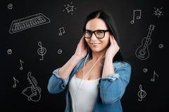 Positive Frau, die Musik hört und glücklich schaut Lizenzfreie Stockfotos