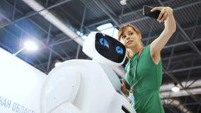 Positive Frau, die selfies mit Roboter macht Das Mädchen macht selfie mit einem Roboter Nette Frau, die Bewegungen nach Roboter w stock video