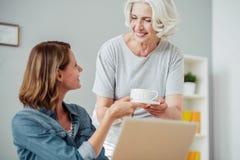 Positive Frau, die am Tisch sitzt Lizenzfreie Stockfotos