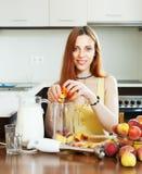 Positive Frau, die von den Pfirsichen kocht Stockfoto