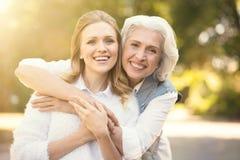 Positive Frau, die Weg mit älterem Elternteil auf der Straße genießt lizenzfreie stockfotos