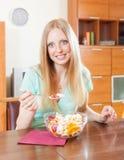 Positive Frau, die zu Hause Obstsalat isst Stockbild