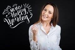 Positive Frau in einer weißen Bluse lächelnd beim Haben eines guten Tages Lizenzfreie Stockfotografie