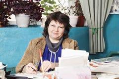 Positive Frau am Schreibtisch lizenzfreie stockfotos