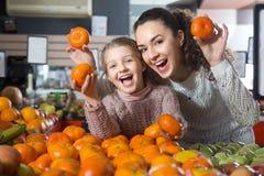 Positive Frau und blondes kleines Mädchen, die whith Mandarine aufwirft Stockfotografie