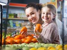 Positive Frau und blondes kleines Mädchen, die whith Mandarine in d aufwirft Lizenzfreie Stockfotos
