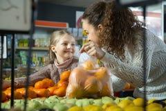 Positive Frau und blondes kleines Mädchen, die whith Mandarine in d aufwirft Stockfotos