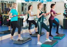 Positive Frauen, die auf aerober Schrittplattform ausarbeiten Lizenzfreie Stockbilder