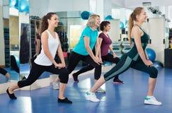 Positive Frauen, die an der aeroben Klasse in der modernen Turnhalle ausarbeiten Lizenzfreies Stockfoto