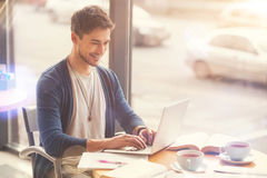 Positive freelance student sitting in the cafe. Combine studying and work. Cheerful handsome student using laptop and working as a freelancer while sitting in Royalty Free Stock Image