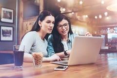 Positive Freundinnen, die den Laptopschirm betrachten lizenzfreie stockfotos