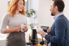 Positive friendly colleagues talking to each other. Pleasant communication. Positive friendly delighted colleagues talking to each other and having coffee while Stock Photo