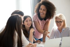 Positive friendly diverse team employees talking laughing at company meeting. Positive friendly african and caucasian creative team employees talking laughing at royalty free stock photo