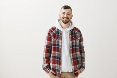 Positive friendly urban european guy with stylish haircut in plaid shirt over hoodie, standing with hands in pockets and. Smiling broadly, feeling uncofident Royalty Free Stock Images