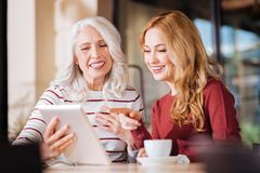 Positive friendly women laughing while looking at the screen of a tablet. So funny. Friendly cheerful positive women of different age sitting at the table and stock image