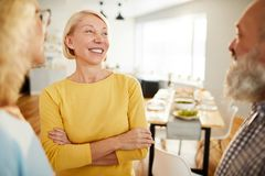 Positive friends chatting in dining room. Group of positive excited mature friends in casual clothing standing in circle and chatting together in dining room royalty free stock image