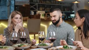Positive friends enjoying appetizing dinner and wine together. Medium close up shot on 4k RED camera