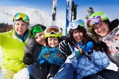 Positive friends with kid together wear ski masks. Positive friends with kid sitting together and wear ski masks Stock Photo