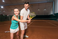 Positive Friends Learning To Play Tennis Royalty Free Stock Photos