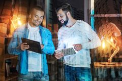 Positive friends looking excited while comparing their amazing gadgets. Comparing devices. Cheerful friendly young men smiling and feeling interested while Stock Image