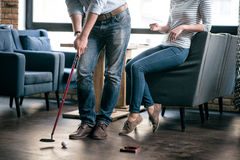 Positive friends playing golf inside Royalty Free Stock Photo